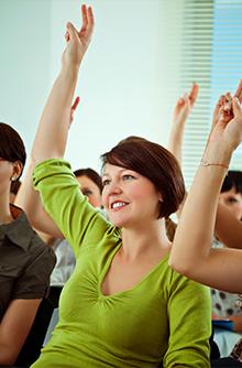 woman raising hand in class